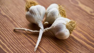 close-up-photo-of-three-garlic-on-wooden-surface-1460862